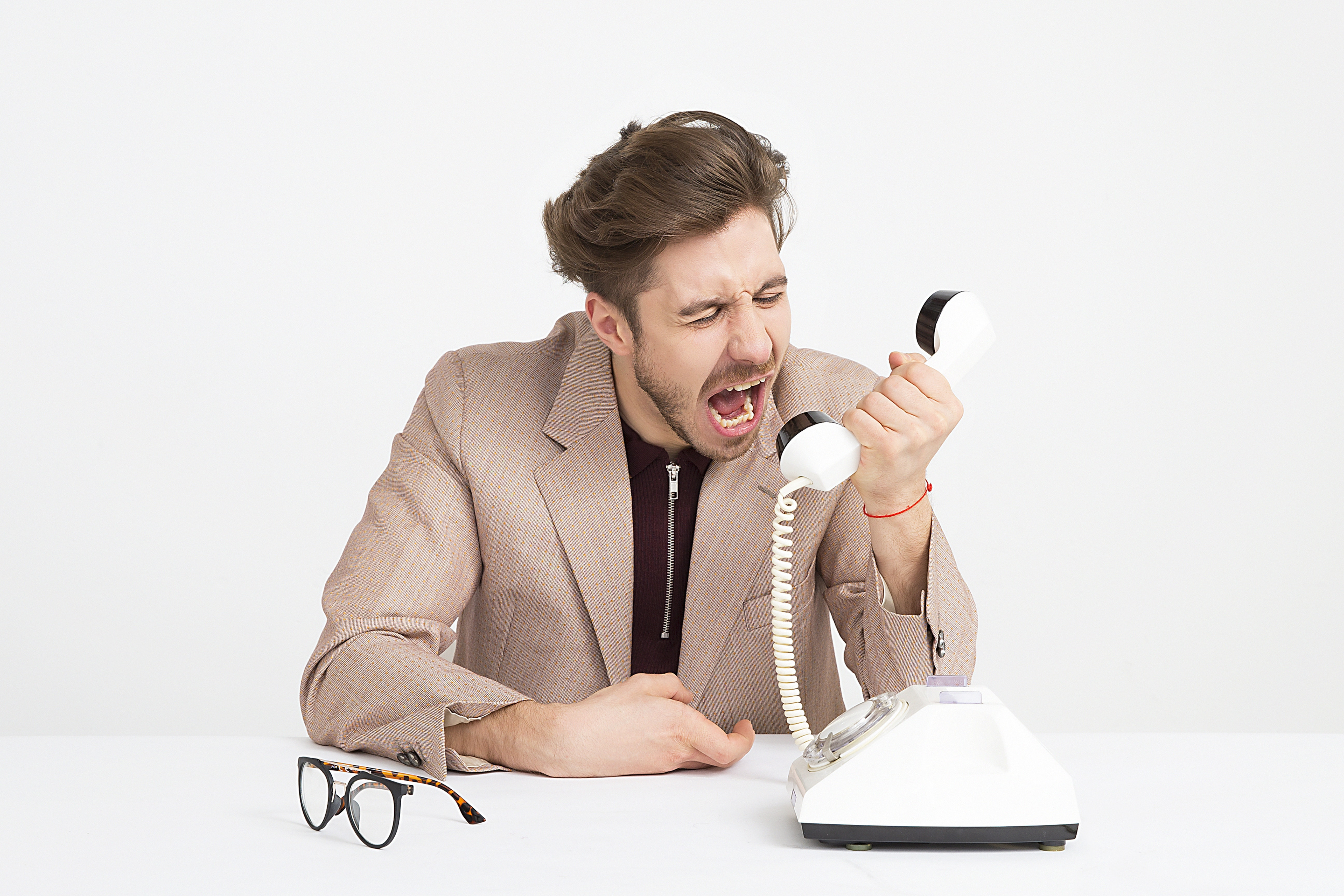 Young man in brown suit yelling into a rotary phone.