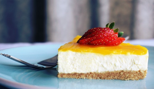 Slice of cheesecake with strawberry on top.
